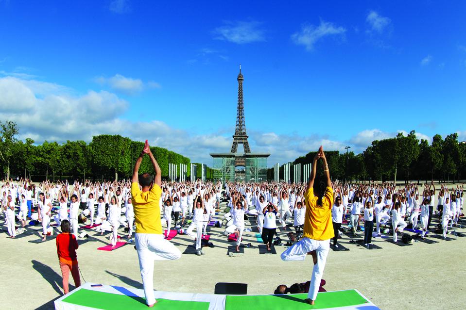 Cientos de personas interpretando el emblemático Surya Namaskar cerca de la Torre Eiffel en París.
