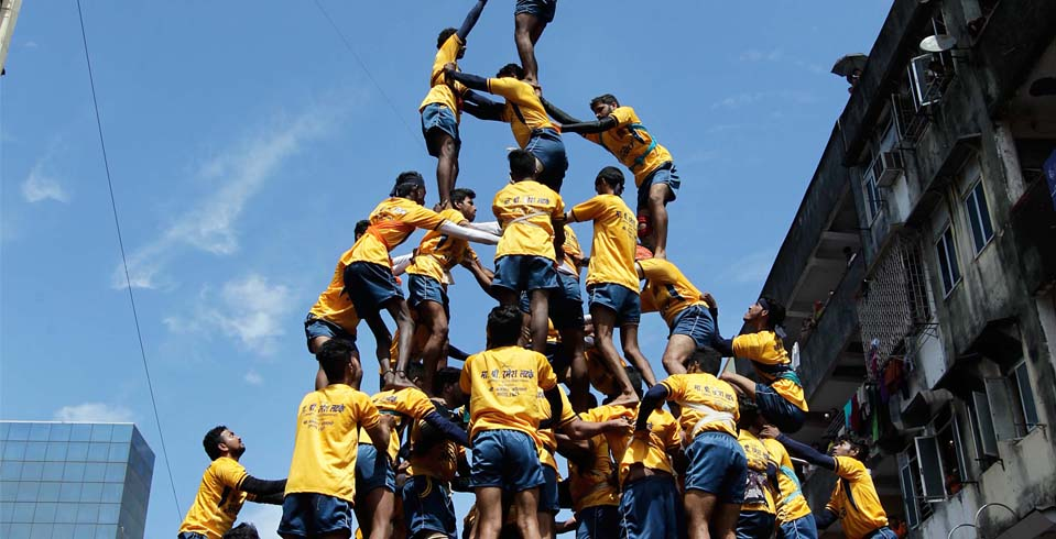 Youth tumble in an attempt to form a human pyramid to break the dahi handi, in Mumbai