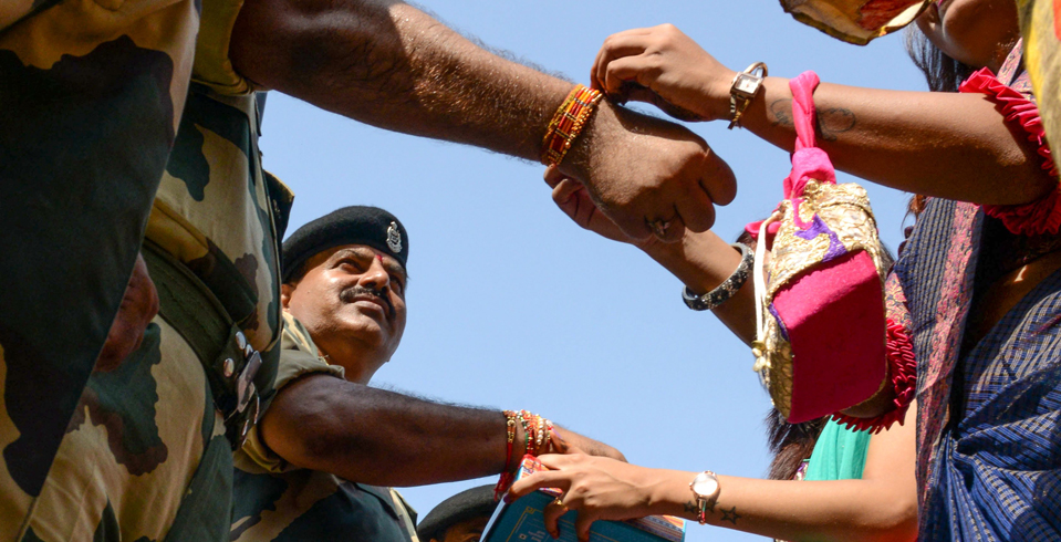 Women tie 'rakhi' (sacred threads) on the wrists of Border Security Force (BSF) personnel during a ceremony observing the festival of Raksha Bandhan at the India-Pakistan Wagah Border Post about 35kms from Amritsar on August 15, 2019.