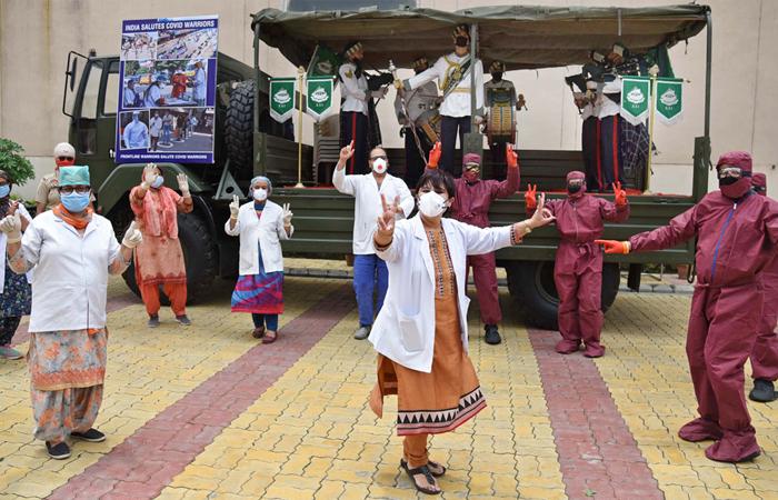 alcuni medici e il personale sanitario danzano davanti a una banda dell'esercito in una stazione di quarantena, per rendere omaggio a coloro che sono coinvolti nella lotta contro la diffusione di COVID-19, ad Amritsar, in Punjab