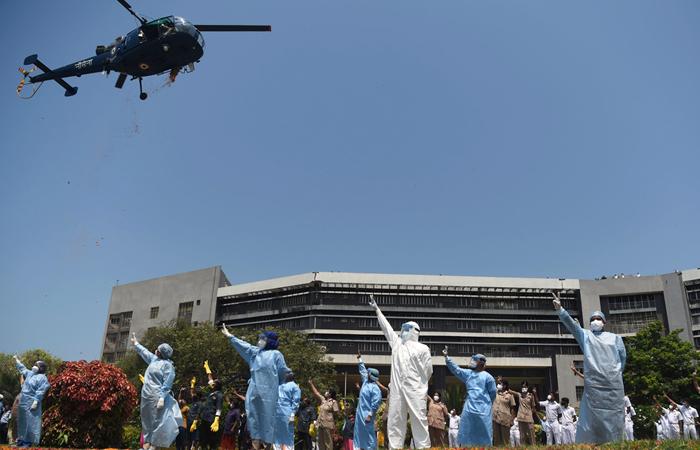 Um helicóptero da Marinha indiana deixa cair pétalas de rosa sobre pessoal do INHS Asvini (Hospital Naval da Índia) para prestar homenagem aos trabalhadores médicos da linha de frente