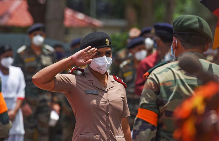 Um membro dos Serviços de Enfermagem Militar saúda um idoso antes de ser felicitado pelos seus serviços durante uma cerimónia de acção de graças no Hospital da Base do Exército, Nova Deli