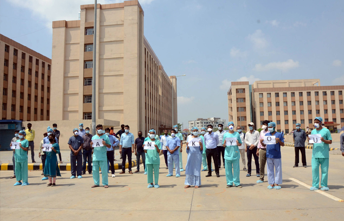 Medical professionals assemble as an IAF chopper approaches to shower flower petals over the Patna AIIMS on May 3, to thank them for their fight against coronavirus at the frontlines