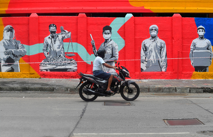 A motorist drives past a wall mural painted to thank frontline workers fighting against the spread of COVID-19 in Mumbai