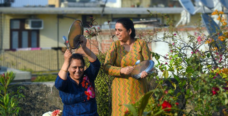 Mulheres em Nova Deli fazem barulho com utensílios de cozina na resposta ao apelo do Primeiro-Ministro Narendra Modi para assinalar a solidariedade com os oficiais de saúde e trabalhadores essenciais a 22 de Março