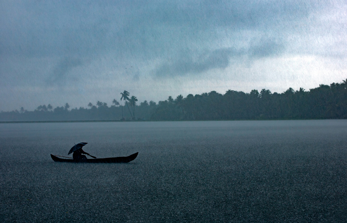 A man rows his boat across a waterway amidst heavy seasonal rainfall near the scenic town of Alappuzha in Kerala