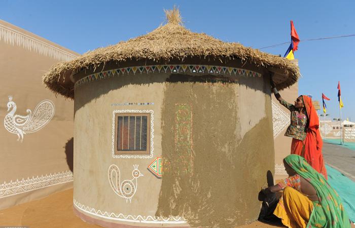Des femmes de la région appliquent une nouvelle couche de boue sur une hutte du village de Dhordo. Dans le cadre de l'expérience générale gujarati, les visiteurs se voient offrir un hébergement dans ces huttes traditionnelles appelées bunga ou bhunga