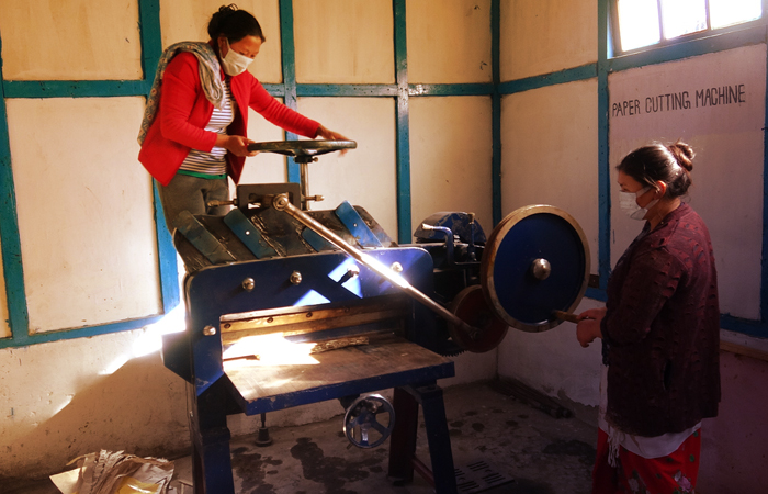 Local women artisans working on the pressing machine at the centre.