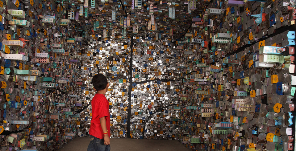 One of Kiran Nadar Museum of Art's treasured art pieces is an installation titled 8'x 12'′ (2009) by late Indian artist Hema Upadhyay. It is an interactive piece created using maquettes of tin houses made from aluminium sheets, car scraps, enamel paint, tarpaulin, pieces of metal, and other objects collected from Dharavi in Mumbai